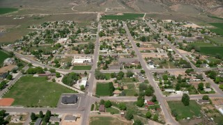 AX130_170 - 6K stock footage aerial video of flying by small rural town, surrounded by farmland, Aurora, Utah