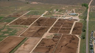 AX130_174 - 6K stock footage aerial video of flying by large cattle ranch, surrounded by fields, Aurora, Utah