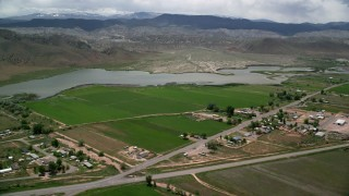 AX130_179 - 6K stock footage aerial video of passing a rural town, farmland and Rocky Ford Reservoir, Sigurd, Utah