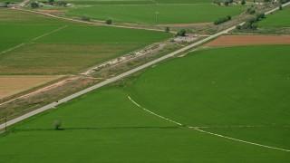 AX130_180 - 6K stock footage aerial video of following Route 118 through farmland, circular crop fields, Sigurd, Utah