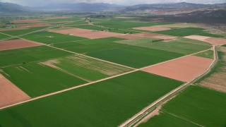 AX130_185 - 6K stock footage aerial video pan across and fly over farmland, rural roads, Venice, Utah