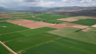 AX130_186 - 6K stock footage aerial video of flying over farmland, mountains in the distance, Richfield, Utah