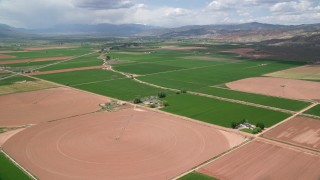 AX130_187 - 6K stock footage aerial video fly over farmland, pan to Route 118, Richfield, Utah