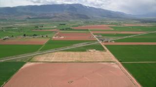 AX130_188 - 6K stock footage aerial video pan across farmland, Route 118, Richfield, Utah