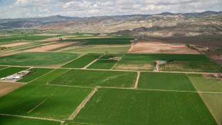 AX130_190 - 6K stock footage aerial video of passing by farmland, brown hills, Richfield, Utah