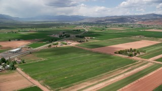 AX130_191 - 6K stock footage aerial video of flying over farmland near Route 118, approach rural town, Richfield, Utah