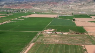 AX130_192 - 6K stock footage aerial video of flying by barns, farmhouses and fields, Richfield, Utah