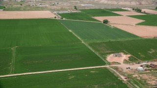 AX130_193 - 6K stock footage aerial video of lying by farmhouse and green fields, Richfield, Utah