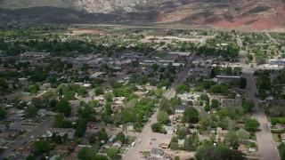 AX130_194 - 6K stock footage aerial video of flying by small town neighborhoods, street with shops, Richfield, Utah