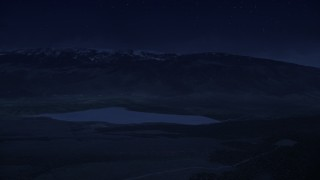 AX130_210_DFN - Aerial stock footage of 4K day for night color corrected aerial footage flyby Koosharem Reservoir, snowy mountains in background, Fishlake National Forest, Utah