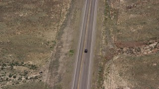 AX130_236 - 6K stock footage aerial video of tracking a black SUV, country road, dry land, Loa, Utah