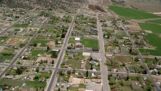 AX130_237 - 6K stock footage aerial video of flying by small rural town near hills, farmland, Bicknell, Utah