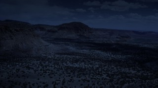 AX130_245_DFN - Aerial stock footage of 4K day for night color corrected aerial footage of flying by mesas, pan and approach a butte, Capitol Reef National Park, Utah