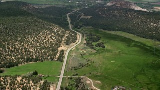 AX130_364 - 6K stock footage aerial video of flying by Route 12, green fields, hills covered in vegetation, tilt to reveal small town, Boulder, Utah
