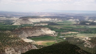 AX130_366 - 6K stock footage aerial video of flying by rural town, green fields, rounded mountains, trees, Boulder, Utah