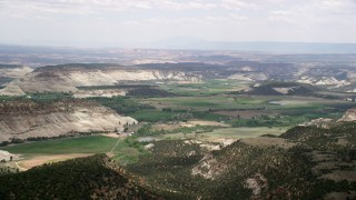 AX130_367 - 6K stock footage aerial video of flying by rural town, rounded mountains, green fields, Boulder, Utah