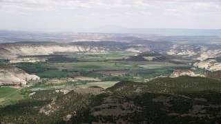 AX130_368 - 6K stock footage aerial video flyby small rural town surrounded by rounded mountains, green fields, Boulder, Utah
