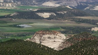 AX130_369 - 6K stock footage aerial video of flying by rural town, fields, pond, and flat-topped mountain, Boulder, Utah