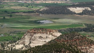 AX130_370 - 6K stock footage aerial video of flying by a rural town, pond, smaller mountains, Boulder, Utah