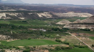AX130_371 - 6K stock footage aerial video of small mountains, green fields, rural town around a pond, Boulder, Utah
