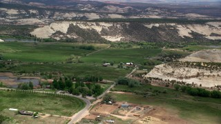 AX130_373 - 6K stock footage aerial video small rural town and pond by mountains, Boulder, Utah