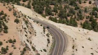 AX130_374 - 6K stock footage aerial video of a bend in Route 12, reveal and track a black SUV, Boulder, Utah