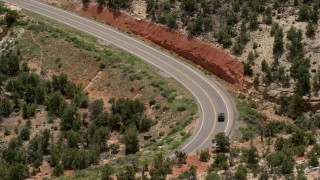 AX130_380 - 6K stock footage aerial video of tracking a black SUV traveling on Route 12 bend, Boulder, Utah