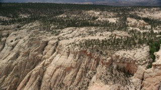 AX130_386 - 6K stock footage aerial video an approach to top of a canyon, desert vegetation, trees, Grand Staircase-Escalante National Monument, Utah