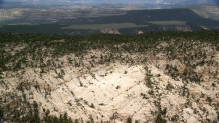 AX130_388 - 6K stock footage aerial video of flying over mountain ridge, approach a distant plateau, Grand Staircase-Escalante National Monument, Utah