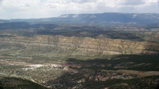 AX130_394 - 6K stock footage aerial video of flying over a valley, approaching a mountain ridge, Grand Staircase-Escalante National Monument, Utah