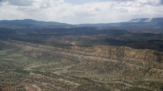 AX130_396 - 6K stock footage aerial video of approaching a mountain ridge from a wide valley, Grand Staircase-Escalante National Monument, Utah