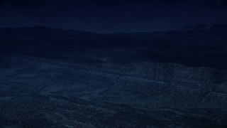 AX130_396_DFN - Aerial stock footage of 4K day for night color corrected aerial footage of approaching a mountain ridge from over a wide valley, Grand Staircase-Escalante National Monument, Utah