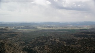 AX130_419 - 6K stock footage aerial video of flying by green valley beyond mountain ridges, Grand Staircase-Escalante National Monument, Utah