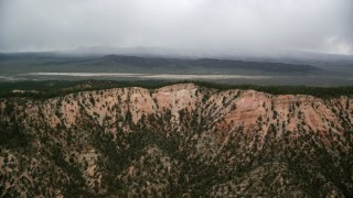 AX130_421 - 6K stock footage aerial video of passing by mountain ridges, trees, dry lake in the distance, Bryce Canyon National Park, Utah