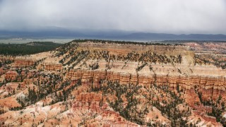 AX130_431 - 6K stock footage aerial video of passing by groups of hoodoos around base of mesa, Bryce Canyon National Park, Utah