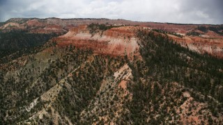 AX130_451 - 6K stock footage aerial video of flying by small mesa with hoodoos, trees, desert vegetation at Bryce Canyon National Park, Utah