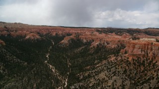 AX130_454 - 6K stock footage aerial video of wide canyon with trees, surrounded by hoodoos, buttes; Bryce Canyon National Park, Utah