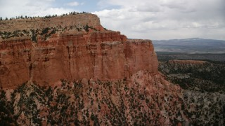 AX130_469 - 6K stock footage aerial video of passing hoodoos on a mesa cliffside, trees and desert vegetation below, Bryce Canyon National Park, Utah