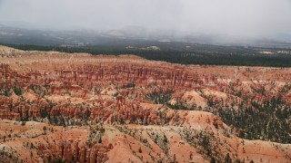 AX130_473 - 6K stock footage aerial video flying near a mesa, tilt to hoodoos, buttes, Bryce Canyon National Park, Utah