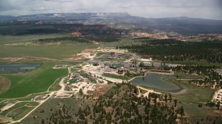 AX130_494 - 6K stock footage aerial video of flying by hotels, surrounded by fields, pond, forest, Bryce, Utah