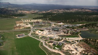AX130_495 - 6K stock footage aerial video orbit small town and hotels near fields, a pond and forest, Bryce, Utah