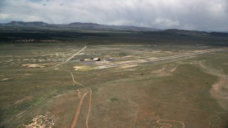 AX130_496 - 6K stock footage aerial video of flying by single runway and wood hangar, Bryce Canyon Airport, Utah