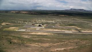 AX130_497 - 6K stock footage aerial video of orbiting single runway, wood hangar, Bryce Canyon Airport, Utah