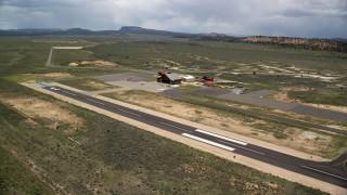 AX130_498 - 6K stock footage aerial video of circling a single runway, wooden hangar, Bryce Canyon Airport, Utah