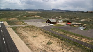 AX130_499 - 6K stock footage aerial video of approaching single prop plane, helicopters, near wooden hangar, Bryce Canyon Airport, Utah