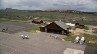 AX130_500 - 6K stock footage aerial video orbit single prop plane and helicopters near a wooded hangar, Bryce Canyon Airport, Utah
