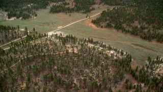 AX131_004 - 6K stock footage aerial video of flying over forest, dirt road, Bryce Canyon National Park, Utah