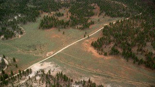 AX131_005 - 6K stock footage aerial video of flying over dirt road and forest, Bryce Canyon National Park, Utah