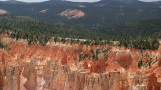 AX131_024 - 6K stock footage aerial video of flying by Pink Cliffs, hoodoos, topped with trees, Bryce Canyon National Park, Utah