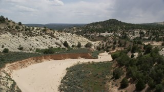 AX131_059 - 6K stock footage aerial video of flying low over dry riverbed, Grand Staircase-Escalante National Monument, Utah